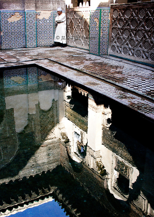 Fes: el Attarine Medersa: reflecting pool in the inner courtyard; Moroccan man in white jellaba, arms folded..