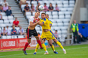 Charlie Wyke (#9) of Sunderland AFC competes with Luke O'Neill (#2) of AFC Wimbledon for a header during the EFL Sky Bet League 1 match between Sunderland and AFC Wimbledon at the Stadium Of Light, Sunderland, England on 24 August 2019.