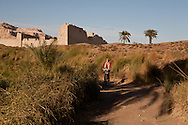 tourist woman on a bike in countryside near Medinet Habou, RAMSES 3 temple in Thebes  Louxor - Egypte    /  femme touriste sur une bucyclette , village et campagne de Medinet Habou, temple de Ramses 3 a Thebes  Louqsor - Egypt