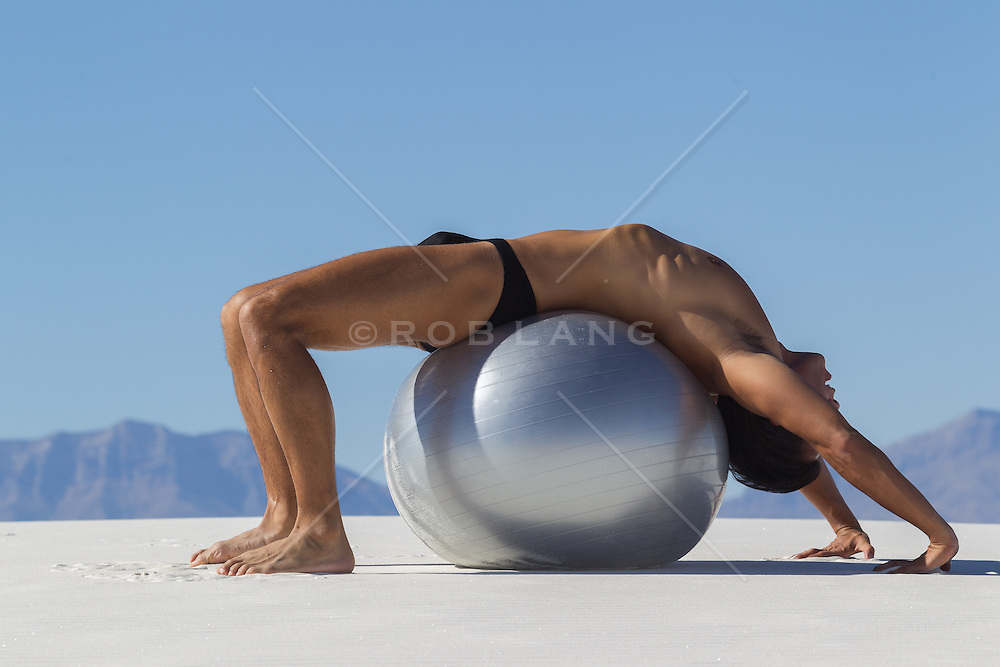 man in a speedo with a large exercise ball in the desert