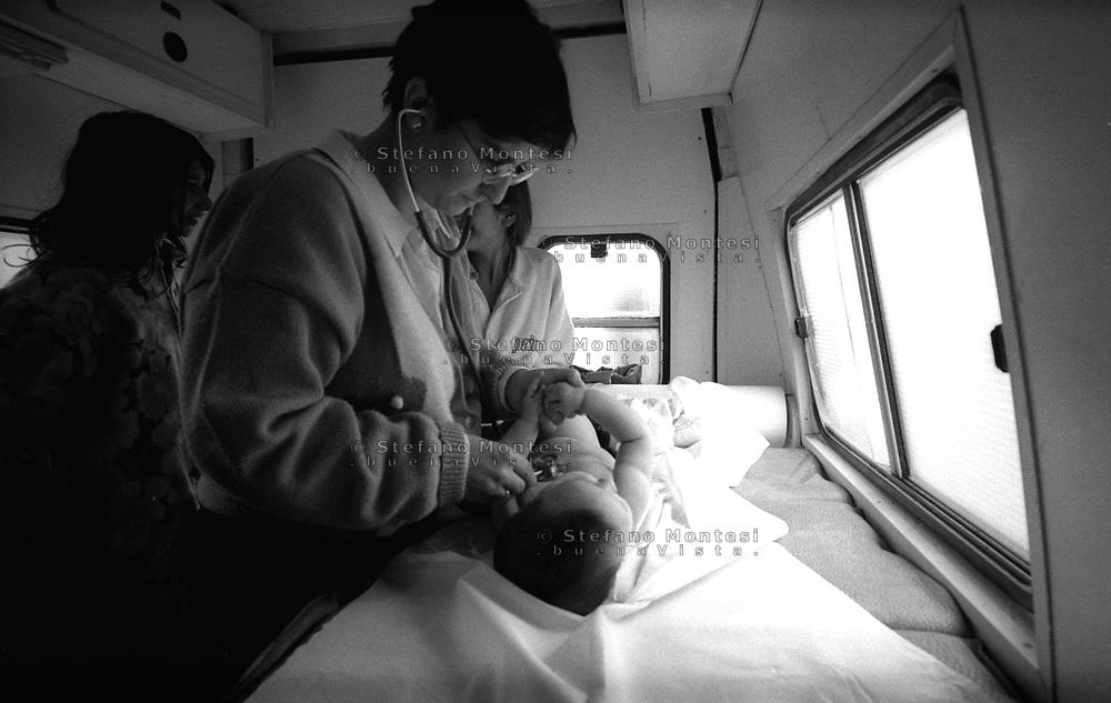 Roma 1996<br /> Servizio Medico Mobile della Caritas diocesana di Roma<br /> Un medico pediatra visita un bambino del Campo rom di Vicolo Savini