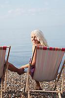 Woman holding man's hand sitting on deckchair on beach
