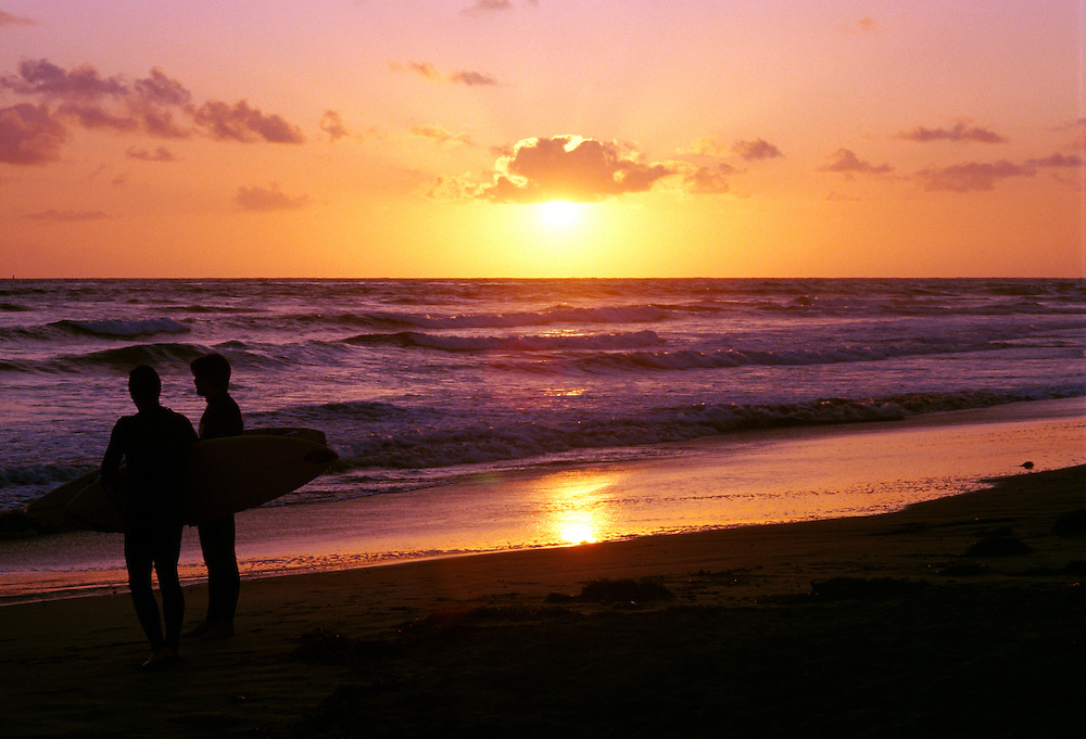 Silhouette of surfers looking out to ocean at Carlsbad State Beach, CA at sunset