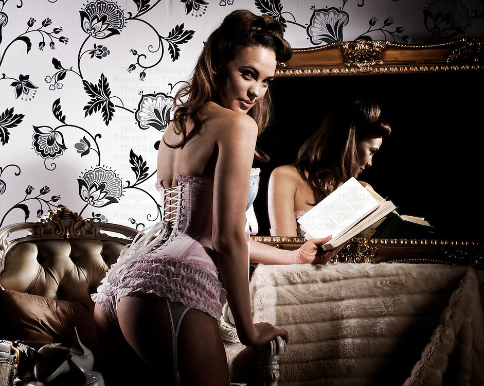 Young female in lingerie holding a book.