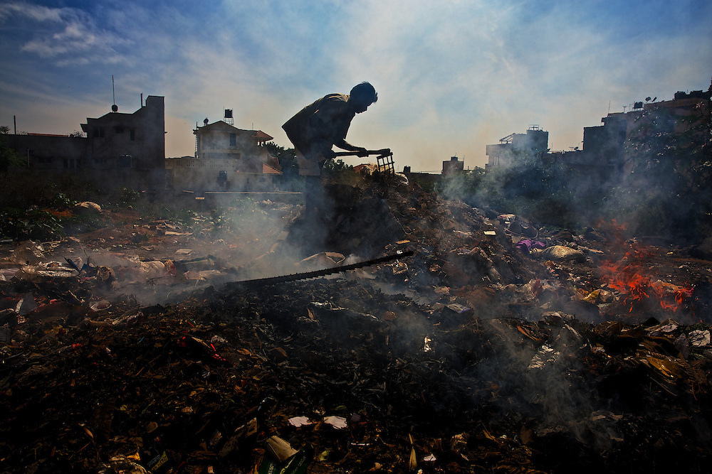 Man working on a rubbish dump, in the Jay Dhuvaneshwer (Nagar) area in Bangalore, India on December 15th, 2012 (Gianluca Colla). Every day hundreds of millions of people in India wake up at dawn and work hard until sunset to find their way out of poverty. Many of these people cannot access clean water and electricity, nor pay school fees for their children or see a doctor when they are sick. Their basic needs have been largely unmet, neither by public services nor by the market that doesn't consider them as potential customers. Access to health care services in India by low-income people is limited due to the poor supply from the public service, especially in remote areas such as slums.