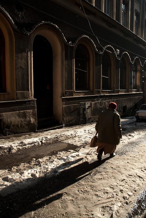 An elderly woman walking through the snow in the city of Cieszyn,  Silesia, Poland. January 2009.