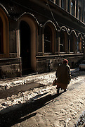 An elderly woman walking through the snow in the city of Cieszyn,  Silesia, Poland. January 2009.