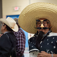 "Chavelo Chavarria, 65, dressed as ""Pancho"", poses with his tequila and pistol in the Senior Center gym, as he waits his turn for the dart toss game on Wednesday in Gallup."