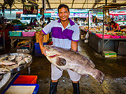 12 JULY 2018 - SAMUT PRAKAN, SAMUT PRAKAN, THAILAND:  A fish monger struggles to hold up a large fish he has for sale in Pak Nam market in Samut Prakan. Fish consumption recently hit a record high according to a report published this week by the United Nations Food and Agriculture Organization. The FAO reported that global fish production peaked at about 171 million tonnes in 2016, 47 percent of it from fish farming. The FAO also reported that global fish consumption between 1961 and 2016 was rose nearly twice as fast as population growth. In 2015, fish accounted for about 17 percent of the animal protein consumed globally. This has ramifications for Thailand, which has one of the world's largest fish and seafood industries. About 90% of Thailand's seafood production is exported, which accounts for about 4% of Thailand's exports.  PHOTO BY JACK KURTZ