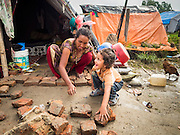 05 AUGUST 2015 - KATHMANDU, NEPAL: A woman and her son put in a brick patio in front of their tent in a large Internal Displaced Person (IDP) Camp in the center of Kathmandu. The camp is next to one the most expensive international hotels in Kathmandu. More than 7,100 people displaced by the Nepal earthquake in April live in 1,800 tents spread across the space of three football fields. There is no electricity in the camp. International NGOs provide water and dug latrines on the edge of the camp but the domestic waste water, from people doing laundry or dishes, runs between the tents. Most of the ground in the camp is muddy from the running water and frequent rain. Most of the camp's residents come from the mountains in northern Nepal, 8 - 12 hours from Kathmandu. The residents don't get rations or food assistance so every day many of them walk the streets of Kathmandu looking for day work.      PHOTO BY JACK KURTZ