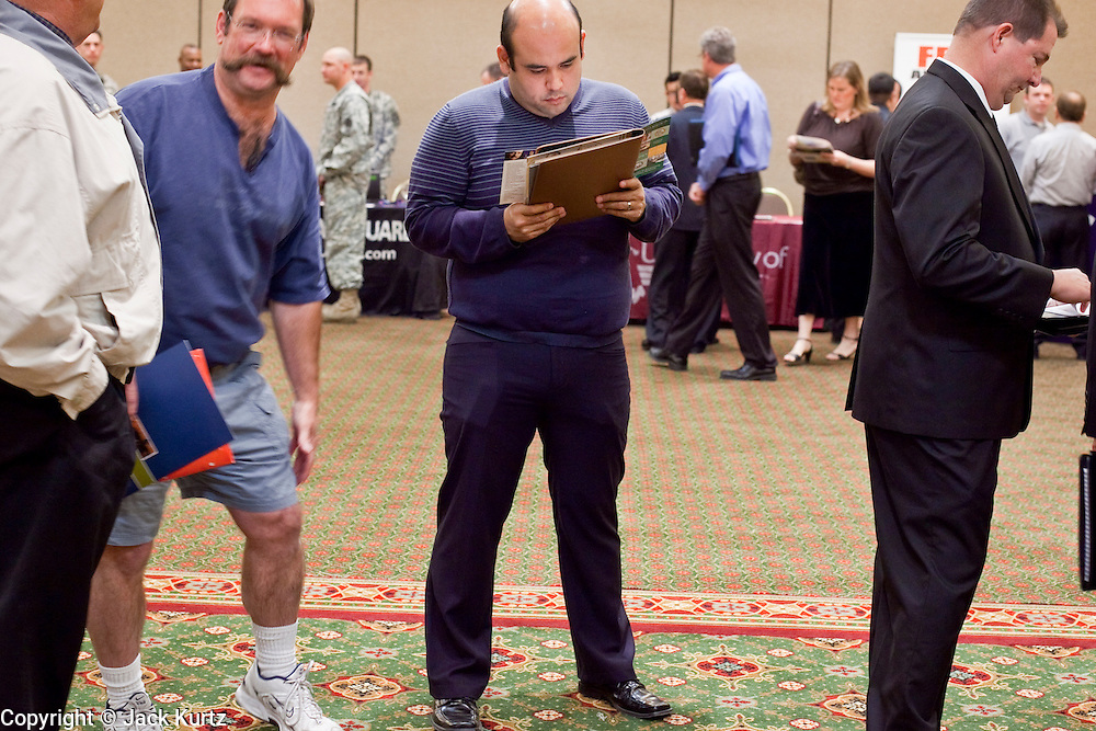 23 February 2009 -- PHOENIX, AZ: MARTIN MONGE, from Tempe, AZ, center, waits with others for a chance to interview at Lockheed Martin at a job fair sponsored by National Career Fairs in the Marriott Hotel in Phoenix Monday. Monge said he's been out of work for about a month. More than 1,500 people lined up for a chance to turn in a resume and be interviewed by the 21 firms who had booths at the job fair. According to the US Bureau of Labor Statistics, unemployment in Arizona increased from 3.9 percent in April 2008 to 6.9 percent in December 2008.    Photo By Jack Kurtz / ZUMA Press