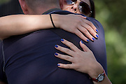 A woman with blue painted nails holds on tight to her partner in a public street.