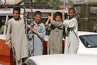11 AUG 2003, KABUL/AFGANISTAN:<br /> Jungen fahren aussen an einem Kleinbus durch die Strassen von Kabul<br /> IMAGE: 20030811-01-013<br /> KEYWORDS: Junge, Kind, child