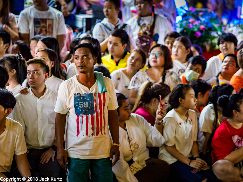 19 OCTOBER 2018 - BANGKOK, THAILAND: People wait for Hindu holy men to walk past them during a Navratri procession in Bangkok. Navratri is a nine night (10 day) long Hindu celebration that marks the end of the monsoon and honors of the divine feminine Devi (Durga). The festival is celebrated differently in different parts of India, but the common theme is the battle and victory of Good over Evil based on a regionally famous epic or legend such as the Ramayana or the Devi Mahatmya. Navratri is celebrated throughout Southeast Asia in communities that have a large Hindu population.  PHOTO BY JACK KURTZ