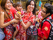 "19 FEBRUARY 2015 - BANGKOK, THAILAND: Women and a girl react to a lion dancer on Chinese New Year in Bangkok. 2015 is the Year of Goat in the Chinese zodiac. The Goat is the eighth sign in Chinese astrology and ""8"" is considered to be a lucky number. It symbolizes wisdom, fortune and prosperity. Ethnic Chinese make up nearly 15% of the Thai population. Chinese New Year (also called Tet or Lunar New Year) is widely celebrated in Thailand, especially in urban areas that have large Chinese populations.    PHOTO BY JACK KURTZ"