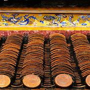 Detail of the roof tiles and paintings on top of a restored building at the Imperial City in Hue, Vietnam. A self-enclosed and fortified palace, the complex includes the Purple Forbidden City, which was the inner sanctum of the imperial household, as well as temples, courtyards, gardens, and other buildings. Much of the Imperial City was damaged or destroyed during the Vietnam War. It is now designated as a UNESCO World Heritage site.