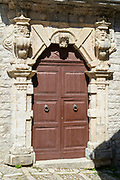Quaint door and arched doorway of stone carvings in historic centre of Erice, Sicily, Italy