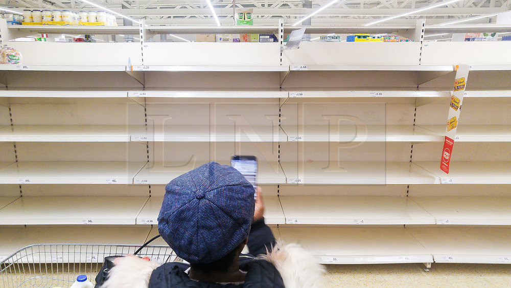 © Licensed to London News Pictures. 03/03/2018. Salford, UK. A shopper takes a photograph of empty shelves, depleted of all stock of bread, at a branch of Sainsbury's supermarket in Salford today as it's reported snow has prompted panic buying of food staples . Photo credit: Joel Goodman/LNP