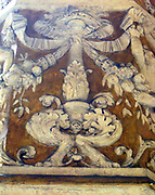 Interior detail from the Palazzo Vecchio, Florence, Italy. A massive, Romanesque fortress-palace designed by the architect Arnolfo di Cambio. Internally, The first courtyard was designed in 1453 by Michelozzo. In the lunettes, high around the courtyard, are crests of the Church and City Guilds. In the centre, the porphyry fountain is by Battista del Tadda. This image shows detail from a column covered in decorative reliefs.