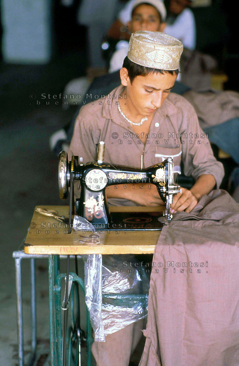 Pakistan Peshawar  1986..Young Afghan Boys in Refugee Camp he works as tailor