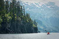 Kayakers paddle along the rocky coast of Prince William Sound, Alaska