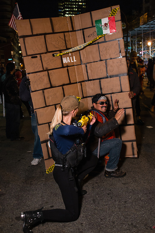New York, NY - 31 October 2016. A pair costumed as a Mexican immigrant and an armed and threatening border patrol agent pose in front of a wall meant to represent Donald Trump's proposed border wall between the U.S. and Mexico.