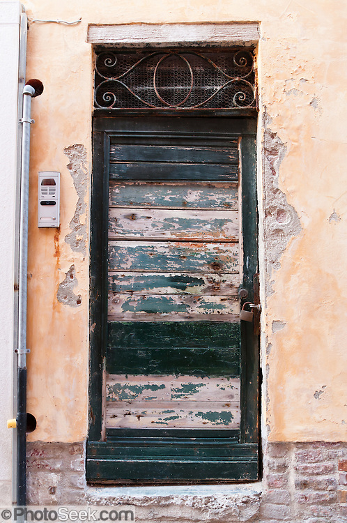 "An old door flakes green paint. Venice (Venezia) is the capital of Italy's Veneto region, named for the ancient Veneti people from the 10th century BC. The romantic ""City of Canals"" stretches across 117 small islands in the marshy Venetian Lagoon along the Adriatic Sea in northeast Italy, between the mouths of the Po (south) and Piave (north) Rivers. The Republic of Venice was a major maritime power during the Middle Ages and Renaissance, a staging area for the Crusades, and a major center of art and commerce (silk, grain and spice trade) from the 13th through 17th centuries. The wealthy legacy of Venice stands today in a rich architecture combining Gothic, Byzantine, and Arab styles. Composer Antonio Vivaldi (1678-1741) was born in Venice."