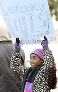 Sha-Tori Boggs, 10, a student at Fairview Elementary School, holds up  sign as she waits for Hillary Clinton to arrive at the Fair River Oaks Council (FROC) office in Dayton, Thursday, February 14, 2008.