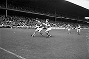 06/09/1964<br /> 09/06/1964<br /> 6 September 1964<br /> All-Ireland Minor Final: Cork v Laois at Croke Park, Dublin.<br /> Cork forward, A. Flynn (left), with the ball in his hand, beathing M. McDonnell (Laois back) to hit the ball towards the goal.