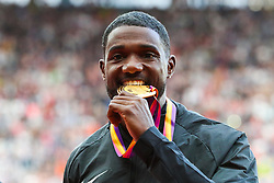 London, 2017 August 06. Men's 100m champion Justin Gatlin bites his medal on the podium on day three of the IAAF London 2017 world Championships at the London Stadium. © Paul Davey.