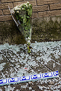 Brussels 23 March 2016 flowers are put at the closed exit of the maalbeek subway. A lot of broken glass of the metro entrance doors on the floor and the m sign of the metro