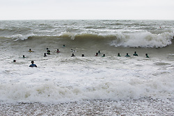 © Licensed to London News Pictures. 18/03/2017. Brighton, UK. Members of the Brighton Surf Life Saving Club brave the cold water and powerful waves to take part in their weekly training session. Photo credit: Hugo Michiels/LNP