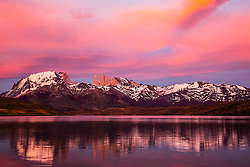 The majestic peaks and spires of Torres del Paine reflected on a blue lake at dawn, Torres del Paine, Chile, South America