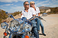 Senior couple wear sunglasses seated on motorcycle on desert road