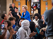 "21 OCTOBER 2019 - DES MOINES, IOWA: US Senator ELIZABETH WARREN (D-MA) ""high fives"" a teacher an assembly for students at Roosevelt High School in Des Moines. Sen. Warren talked to students about her journey from childhood in Oklohoma to running for the US Presidency. Sen. Warren is campaigning to be the Democratic nominee for the US presidency in Iowa this week. Iowa traditionally hosts the the first selection event of the presidential election cycle. The Iowa Caucuses will be on Feb. 3, 2020.                 PHOTO BY JACK KURTZ"