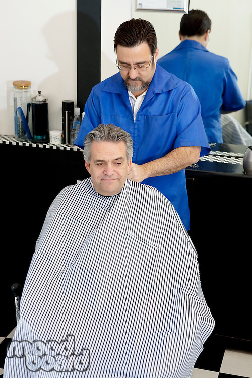 Barber tying cloth before haircut of a mature man