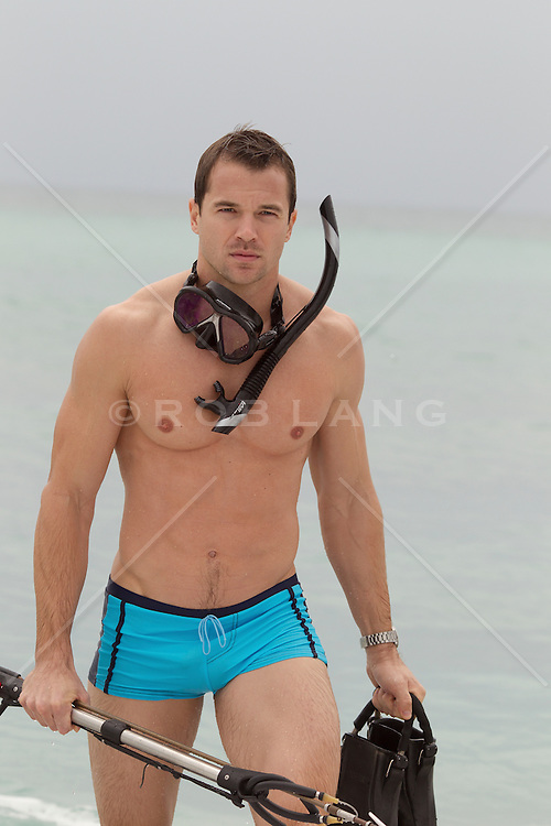 sexy man in James Bond style bathing suit and snorkel gear walking by the ocean in Florida