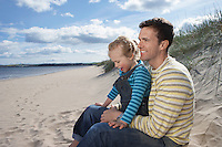 Father embracing daughter (5-6) sitting on beach
