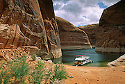We parked our rented houseboat under sandstone cliffs where Willow Gulch meets Lake Powell, in order to hike to Broken Bow Arch, in Glen Canyon National Recreation Area, Utah, USA.