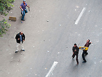 An anti-government protestor, with a makeshift shield, prepares to throw a rock toward attacking pro-government forces on the outskirts of Tahrir Square. (Cairo, Egypt - February 3, 2011)
