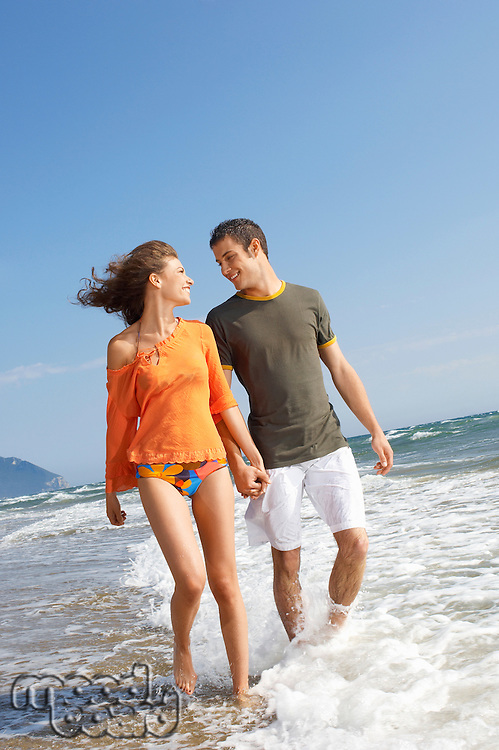 Young couple walking through surf on beach front view