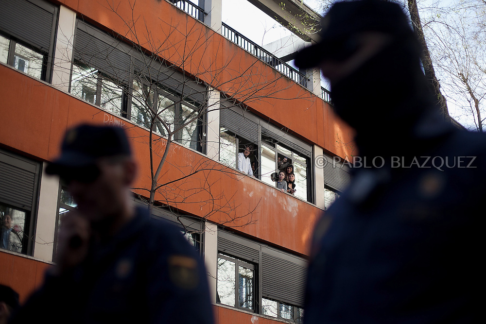 People look at an 'escrache' from a building while riot police stand guard during an 'escrache' near the house of Spain's President of Parliament Jesus Posadas on April12, 2013 in Madrid, Spain. The Mortgage Holders Platform (PAH) and other anti evictions organizations have been organizing 'escraches' for several weeks under the slogan 'There are lives at risk' to claim the vote for a Popular Legislative Initiative (ILP) to stop evictions and facilitate social rent, outside Popular Party deputies' houses and offices. 'Escraches' are a form of peaceful protest that were used in Argentine in 1995 to publically denounce pardoned members of the dictatorship for their crimes at their doorsteps.
