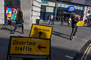 A visitor to London holds a Selfridges department store shopping bag alongside two yellow and black traffic diversion signs during roadworks on the junction of Piccadilly Circus and Regent Street, on 6th March 2020, in London, England.
