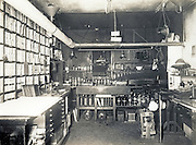 This image shows the interior of the photography darkroom of the United Railroads / Market Street Railway Company around the year 1920. At this point, John Henry Mentz was the photographer. The &quot;U Series&quot; glass plate images are visible in the cabinet with many cubby holes on the left.<br />