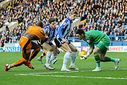 Sheffield Wednesday goalkeeper Keiren Westwood collects the ball as Wolverhampton Wanderers striker Benik Afobe  is held tightly during the Sky Bet Championship match between Sheffield Wednesday and Wolverhampton Wanderers at Hillsborough, Sheffield, England on 20 December 2015. Photo by Simon Davies.