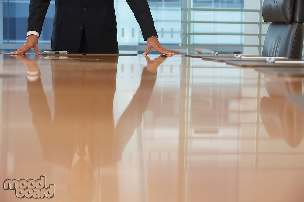 Businessman standing at conference table