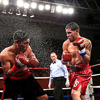 "Emanuel DeJesus fights against Luis Torres (red stripe) during the ""Boxeo Telemundo"" boxing match at the Kissimmee Civic Center on Friday, March 14, 2014 in Kissimmme, Florida. (Photo/Alex Menendez)"
