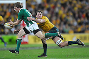 Andrew Trimble sets to pass to support out wide under the pressure of Rocky Elsom's tackle during action from the Rugby Union Test Match played between Australia and Ireland at Suncorp Stadium (Brisbane) on Saturday 26th June 2010 ~ Australia (22) defeated Ireland (15) ~ © Image Aura Images.com.au ~ Conditions of Use: This image is intended for Editorial use as news and commentry in print, electronic and online media ~ Required Image Credit : Steven Hight (AURA Images)For any alternative use please contact AURA Images