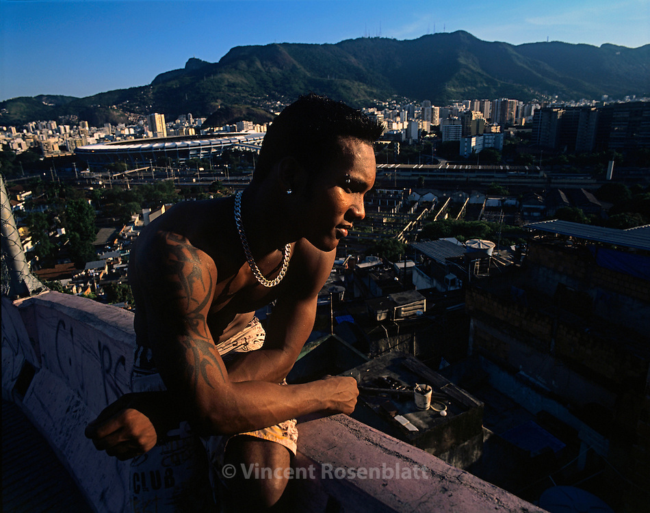 "Mangueira favela, Rio de Janeiro.  Diego, leader of the boys band ""Muleks 100 limits"" (""boys without limits"") looks at Mangueira slum, from the heights of the hill, dreaming that his group ""Muleks 100 limits"" will have success on the carioca funk scene.  In the background on the left, one can see the mythical Maracana stadium."