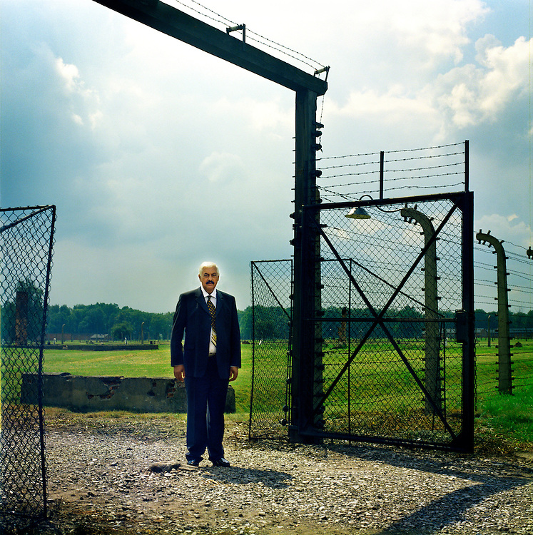 Hugo, a German survivor stands in the gate of the special Roma camp in Auschwitzh - Birkenau. As a child Hugo passed through many camps including Auschwitz before he was liberated by the British from Bergen-Belsen.